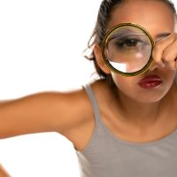 a suspicious young woman looks through a magnifying glass