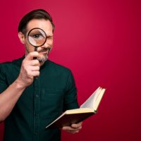 Photo of concentrated focused man looking at you through loupe using book to examine your knowledge isolated vivid color background